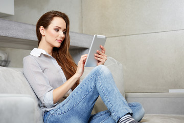 Attractive woman using digital tablet on sofa