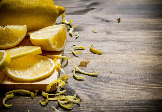 Cut the lemon zest on the Board. On wooden table.