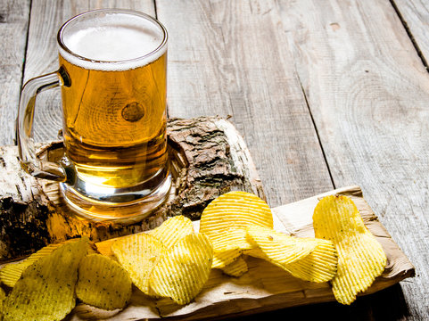 The beer style . Glass of beer on birch stand and chips on wooden background.