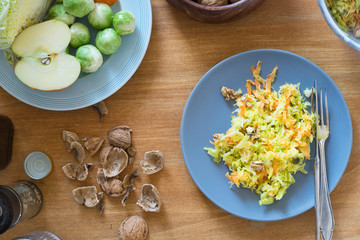 Savoy cabbage, brussels sprouts, apple, carrot and walnut salad on plate surrounded by ingredients