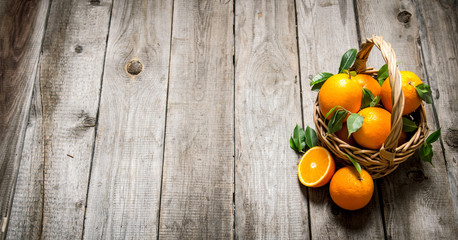 Fresh oranges in the basket with leaves.