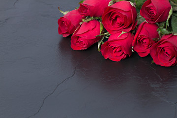 Red roses on black stone background. Valentine's day background.