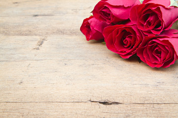 Red roses on woonden background. Valentine's day background.