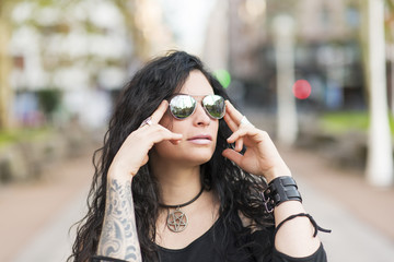 Urban portrait of woman with tattoo and sunglasses heavy metal style.