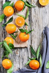 Fresh tangerines with leaves on a rustic wooden table.Selective focus.