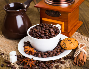 Cup and saucer filled with coffee beans and cane sugar