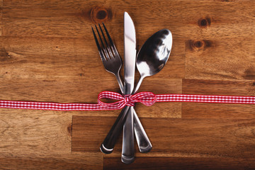 Valentines day set with silverware on wood background