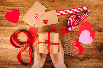 Hearts, gift, ribbons, envepopes on wood background. Woman's hands making handmade valentines day decoration