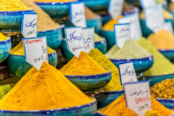 Exposed spices with prices in the store on the Vakil Bazaar in the Shiraz city centre, Iran.