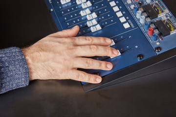 Hand of an audio engineer on a mixing console