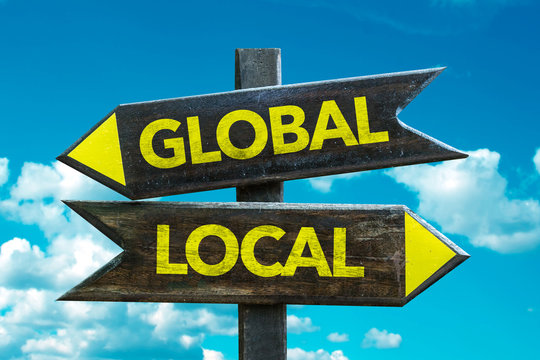 Global - Local signpost with sky background