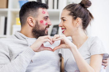 Man and woman connected with his fists in the form of heart. Man with kisses marks on his face.