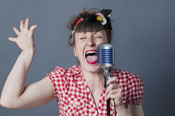 fifties singer in studio - screaming 30s female rocker and vocal artist with retro style performing in old fashioned micro, gray background.....