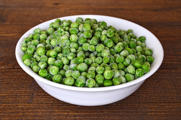 Bowl of frozen peas on wooden table