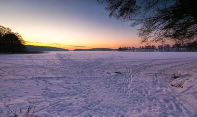 Sunset sky over frozen and snowy lake.