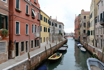 Yellow boat on small canal in Venice, Italy
