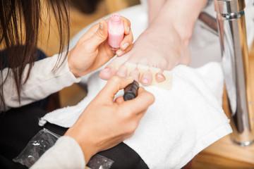 Painting toenails at a nail spa