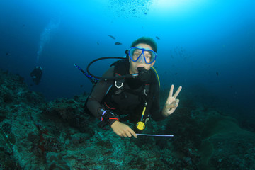 Scuba diving exploring coral reef Similans Thailand