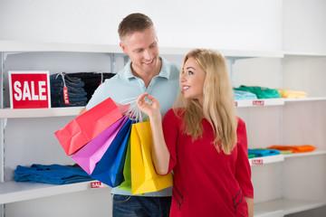 Man Looking At Woman Carrying Shopping Bags