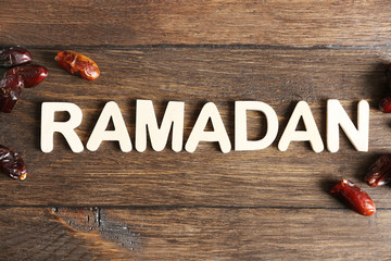 Image of word RAMADAN and dates fruit on wooden background, close up