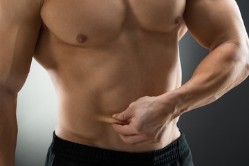 Midsection Of Muscular Man Holding Fat Belly