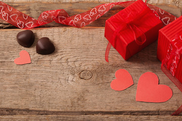 valentine gift box and red heart shapes on wooden board