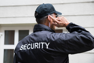 Security Guard Listening To Earpiece Against Building