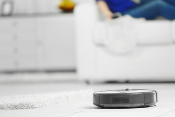 Robotic vacuum cleaner cleaning the room while woman resting on sofa closeup