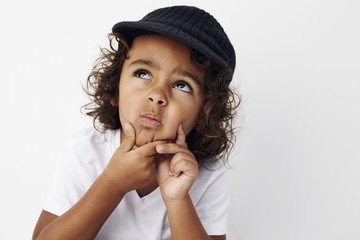 Cool young boy deep in thought against white background