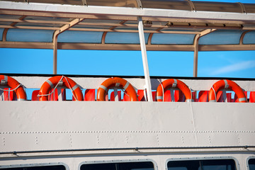 Lifebuoys in a Ferry Boat / A row of red and orange life buoys on the deck of a passenger ship