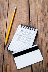 note and pencil, a shopping list for the holidays, credit card