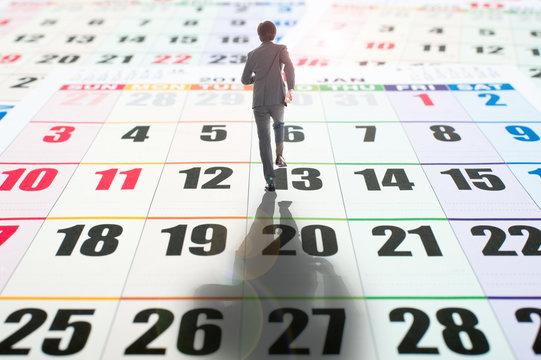 カレンダーの上を歩くビジネスマン