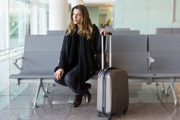Attractive woman waiting for flight at the airport in winter