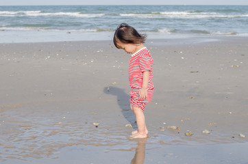 Little child standing alone on the beach