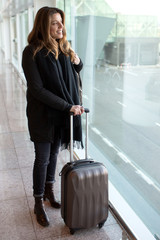 Attractive woman looking for her airplane at the airport in wint