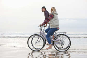 Couple riding bicycles in ocean surf