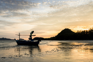 Samroiyod Beach, Thailand, fishing boat parked on the beach,  background is twilight sky at sunrise time with reflection sky