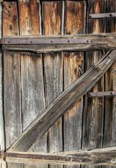 Old wooden weathered door of barn