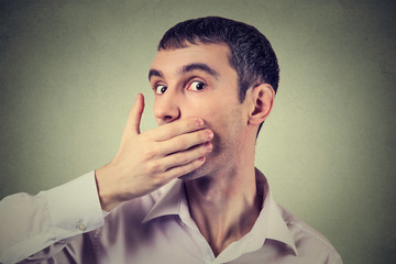 Headshot of a scared adult man with hand covering his mouth