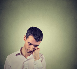 sad, depressed, alone, disappointed man resting his head on hand looking down