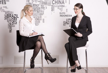 Two business woman on a white background. Business girls sit on the chairs against the wall.