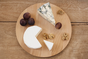 Wooden platter with cheese. Camembert, blue cheese, walnuts, grapes on a wooden board
