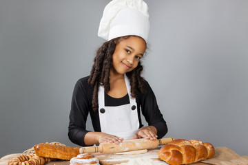 Little dark-skinned girl rolls the dough. The child learns to cook. Clothing and chef hat