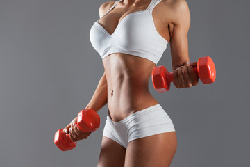 Torso of a young sexy woman lifting dumbbells against gray background