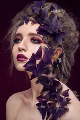 Creative fashionable image, girl with a bright make-up and purple plant on her face.