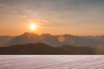 Wood table top on Majestic sunset in the mountains landscape