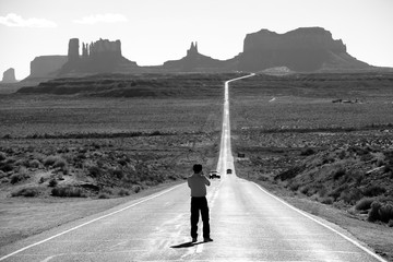 Tourist photographing the famous view from road US 163 in Monument Valley Park, Utah, USA