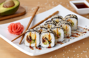Futomaki sushi roll with eel, cucumber, sesame seeds, ginger, and soy sauce.