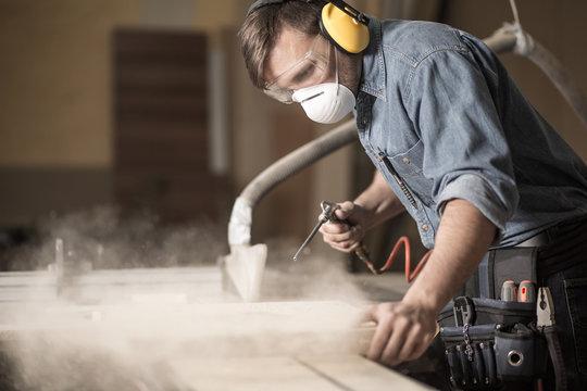 Professionally dressed carpenter varnishing board