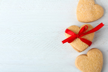 delicious cookies in the shape of a heart with red ribbon on wooden table